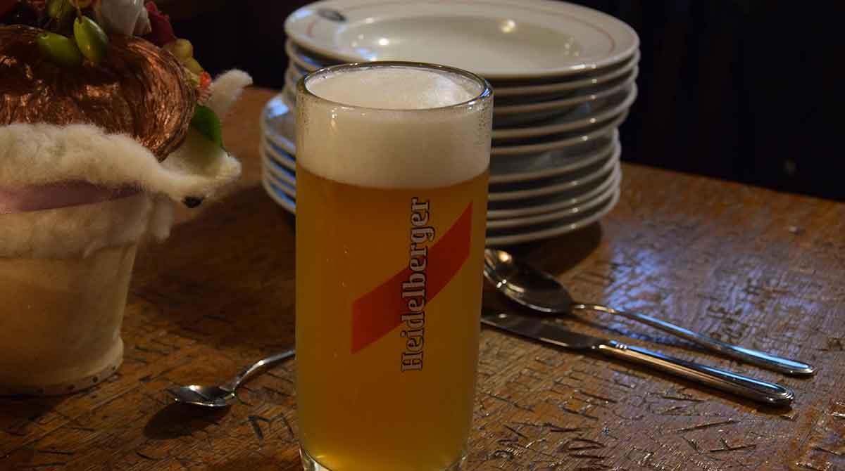 Tisch mit Schnitzereien, gestapelten Tellern und Bier