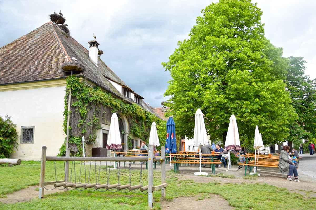 Hof mit Bierbänken, Spielplatz und Storchennestern