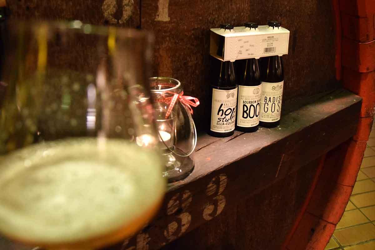 Dreierpack Bier vor Holzfass