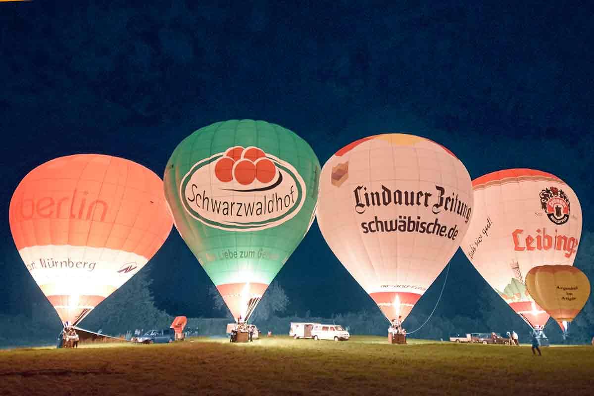 vier erleuchtete Ballons im Dunkeln