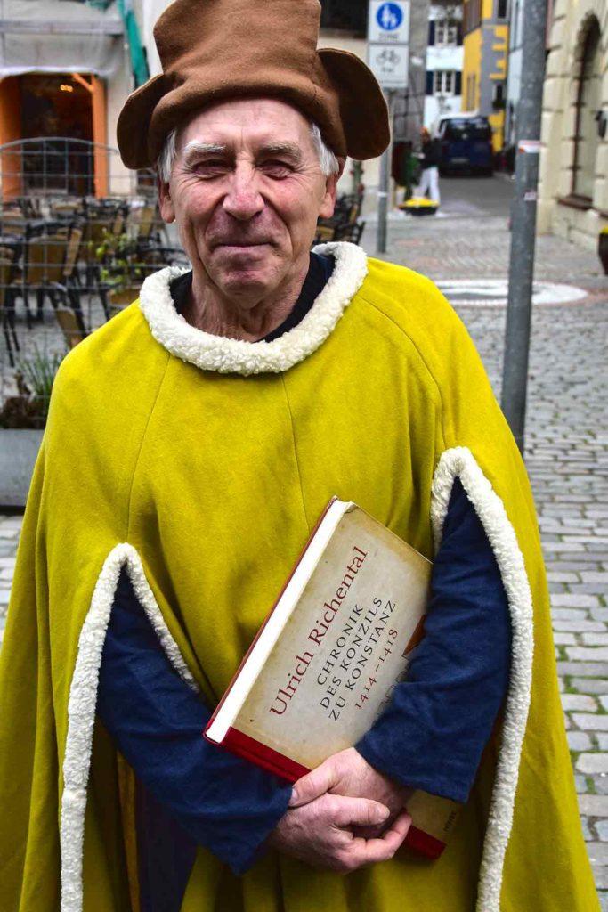Mann in historischem Gewand mit großem Buch