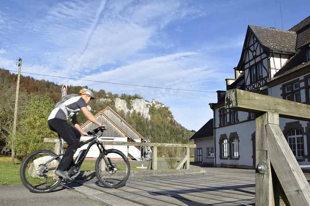 Fahrrad auf Brücke mit Felsen und Schloss im Hintergrnd