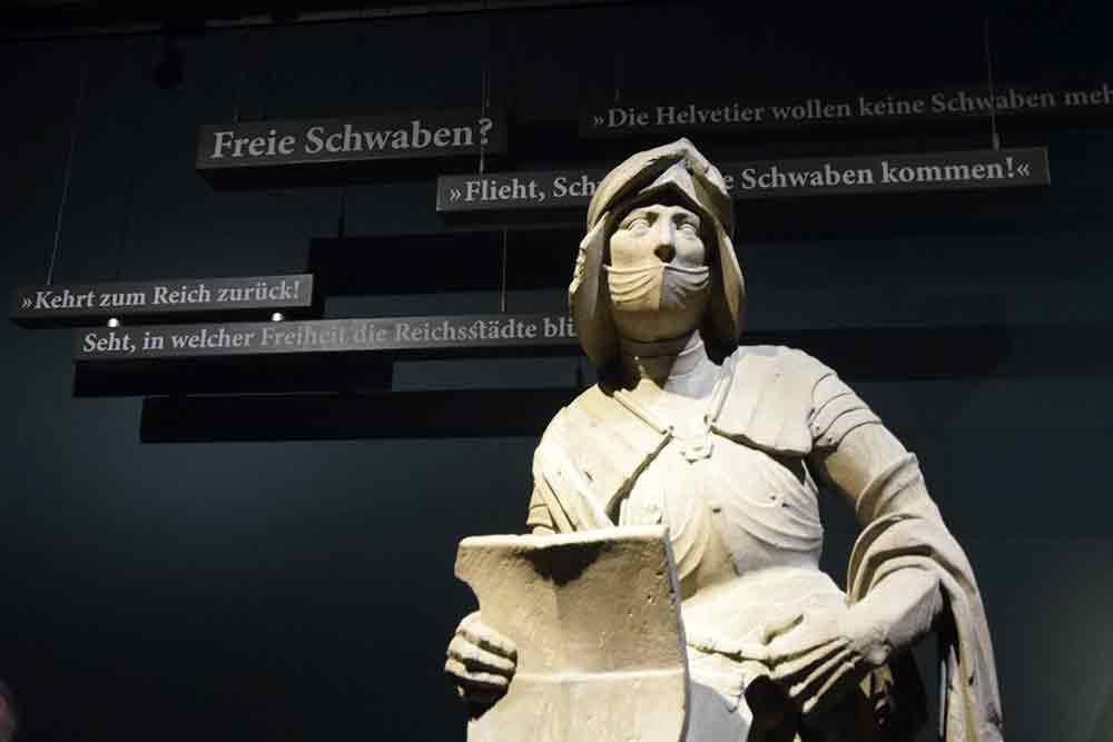 Steinfigur mit Sentenzen im Hintergrund