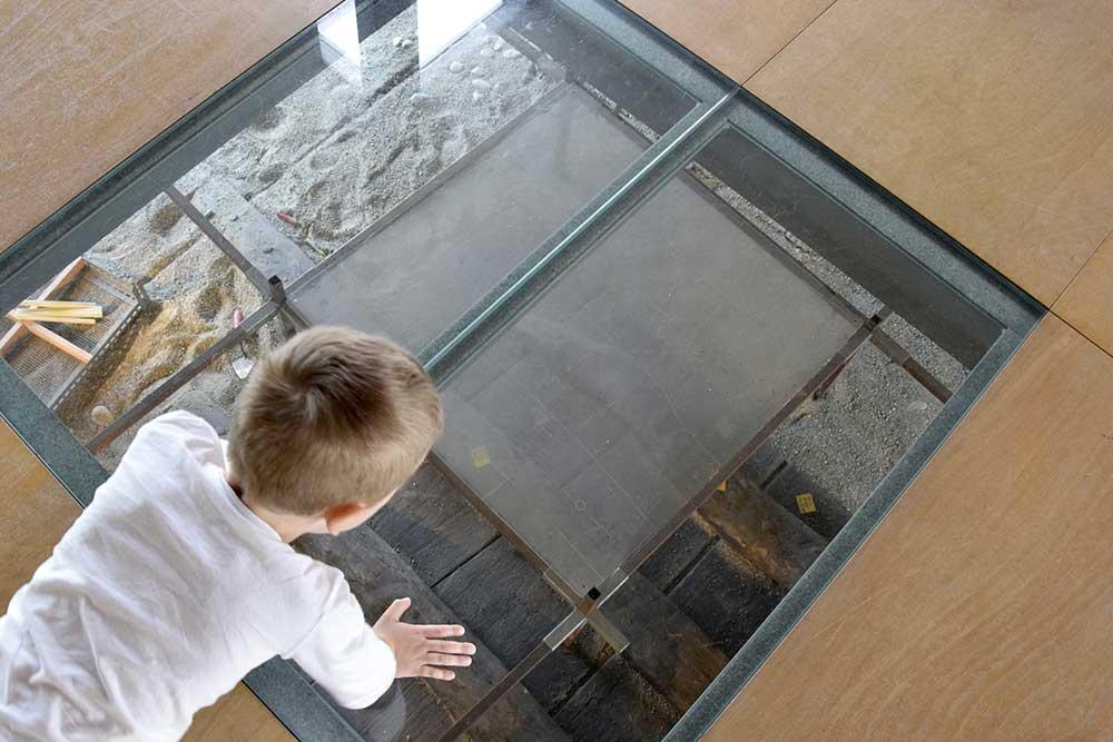 Kind kniet auf Glasscheibe mit Schiffsfund darunter