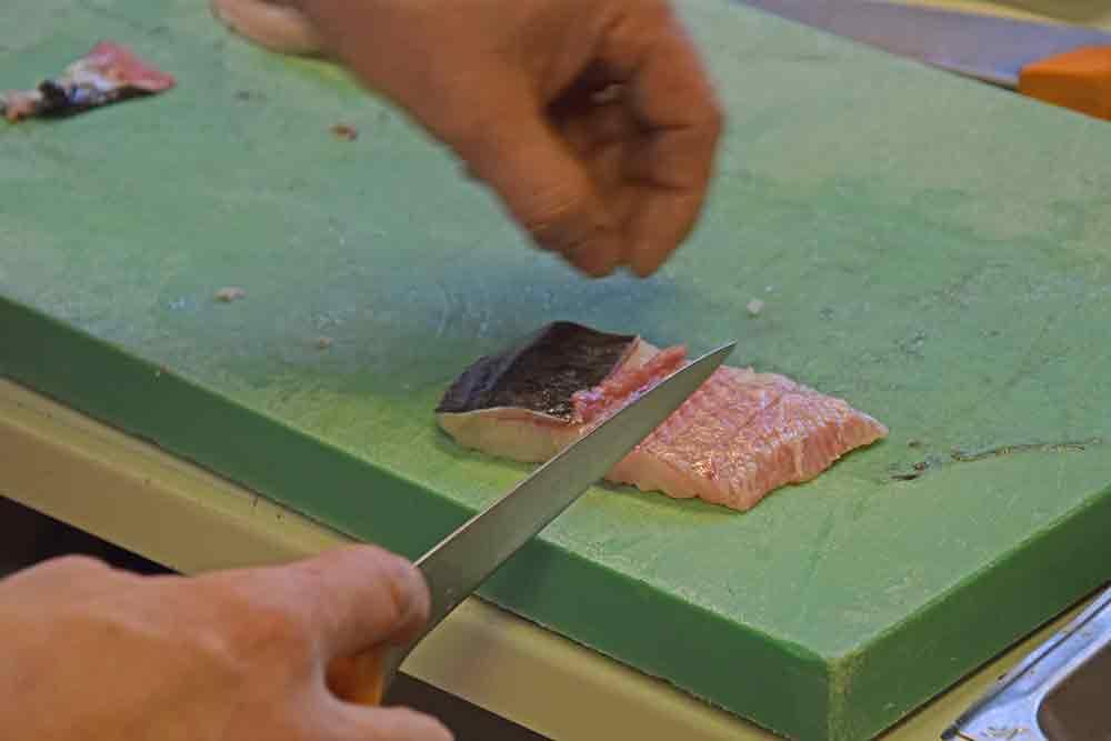 Filet vom Wels wird gehäutet