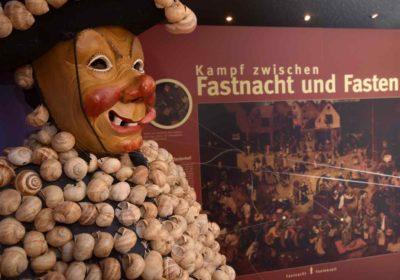 Narrenfigur vor Ausstellungstafel
