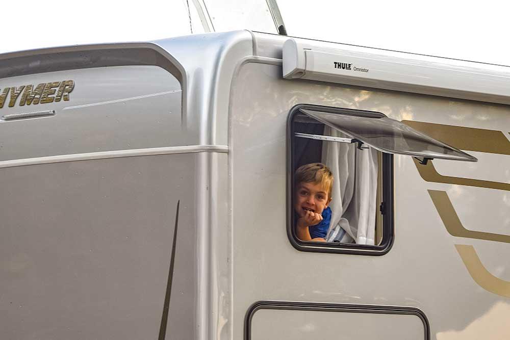 Kind schaut aus Seitenfenster des Hymer ML T 580